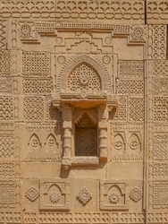 Beautiful traditional intricate geometric and floral carved stone detail on outside wall of a royal mausoleum in UNESCO listed Makli necropolis in Thatta, Sindh, Pakistan