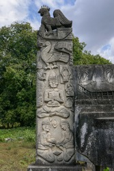 Beautiful traditional megalithic grave headstone carved with rooster, bird, crocodile and men in Pau Rende village, Sumba island, East Nusa Tenggara, Indonesia