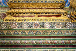 Beautiful traditional mosaic decor with gold color glasses with colorful tiles details from pieces of ceramic on pagoda wall in Wat Phra Kaew temple of Emerald Buddha Bangkok Thailand. Tourism concept