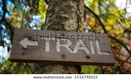 Beautiful trail sign. Trail sign attached to a tree with gorgeous autumn blurred background.