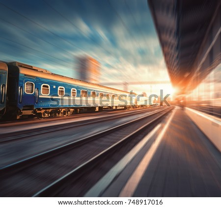Beautiful train with blue wagons in motion at the railway station at sunset. Industrial view with modern train, railroad, railway platform, buildings, cloudy sky with motion blur effect. Concept #748917016