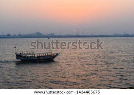 Beautiful tranquil scene of a dhow boat on the calm sea in Doha, Qatar, at sunset. #1434485675