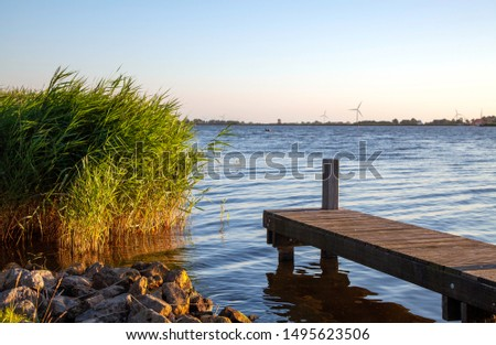 Beautiful tranquil waterscape in warm sunset light in Friesland, The Netherlands. Rocks and reeds on the left, and a scaffolding on the right, showing water and a landscape horizon in the background . #1495623506