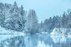 Beautiful tranquil winter scenery. Snowy river coastline. View on frozen lake coast. Trees on the shore covered with snow. Reflection in lake. January scene. Frosty cold winter day. Blue toning.