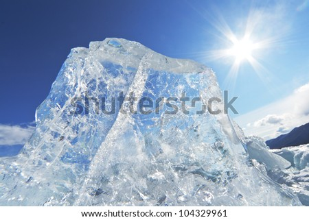 Beautiful transparent ice of Lake Baikal against the clear dark blue sky and a bright sun with rays of light - stock photo