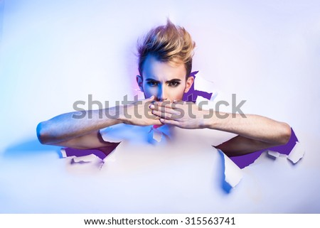 beautiful transvestite with a female make-up breaks through a paper background