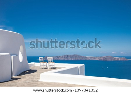 Beautiful travel background, two white chairs with white architecture on Santorini island, Greece. Luxury vacation scenery and summer holiday concept. Perfect tourism landscape, caldera with sea view #1397341352