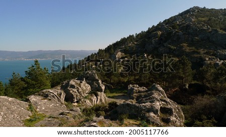 beautiful trekking route between trees and large stones with ascent to Mount Louro peak and views of the sea of Muros Galicia Foto d'archivio ©