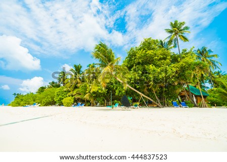 Stock Photo Beautiful tropical beach and sea with coconut palm tree on blue sky in Maldives island - Boost up color Processing