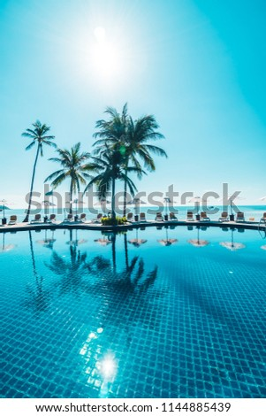 Beautiful tropical beach and sea with umbrella and chair around swimming pool in hotel resort for travel and vacation #1144885439