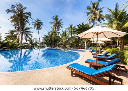 Beautiful tropical beach front hotel resort with swimming pool, sun-loungers and palm trees during a warm sunny day, paradise destination for vacations #567466795