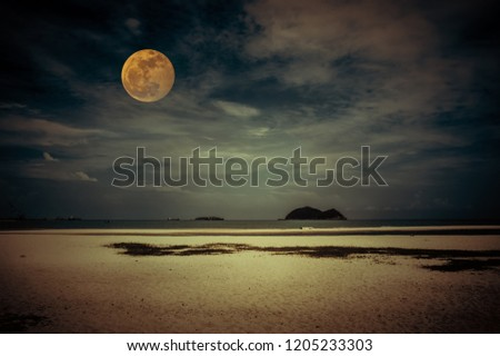Beautiful tropical beach of seascape in night. Attractive bright full moon on dark sky with cloudy. Serenity nature background. Vintage filter effect. The moon taken with my camera.
