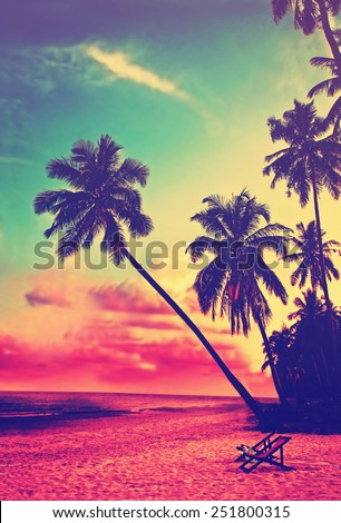Beautiful tropical beach with silhouettes of palm trees at sunset. Travel background with retro vintage instagram filter.