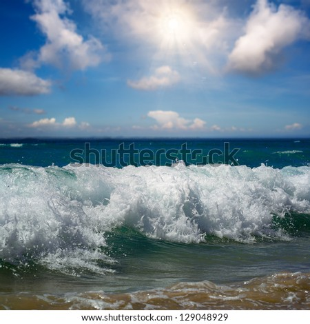 beautiful tropical beach with yellow sand breaking splashing curly wave under bright sunlight