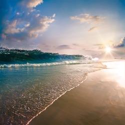 beautiful tropical beach with yellow sand, sun reflections, breaking splashing wave, shorebreak under sunset