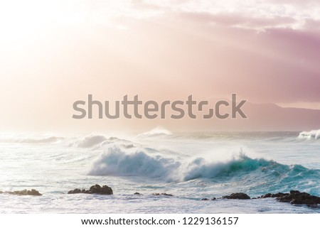 Beautiful Tropical Island Paradise Photo of Clear Aqua Blue Ocean Wave Crashing on Rocks with Sun Rays Coming Though Clouds of Colorful Pastel Sunset Sky at Dusk on Maui Hawaii