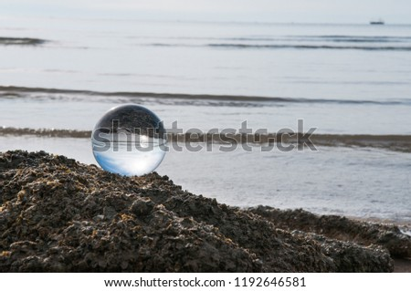 Beautiful Tropical Landscape seen through a Glass Orb. Glass orb by the sea and beach with waves crashing on shore. #1192646581