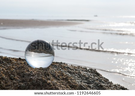 Beautiful Tropical Landscape seen through a Glass Orb. Glass orb by the sea and beach with waves crashing on shore. #1192646605
