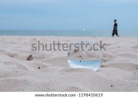 Beautiful Tropical Landscape seen through a Glass Orb. Glass orb by the sea and beach with waves crashing on shore. #1198410619
