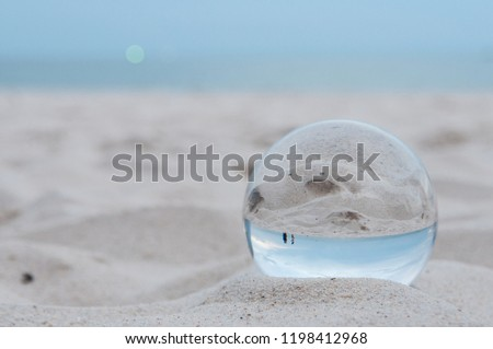 Beautiful Tropical Landscape seen through a Glass Orb. Glass orb by the sea and beach with waves crashing on shore. #1198412968