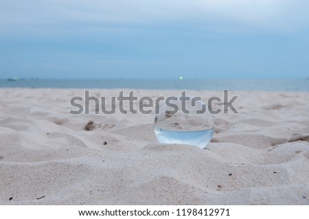 Beautiful Tropical Landscape seen through a Glass Orb. Glass orb by the sea and beach with waves crashing on shore. #1198412971