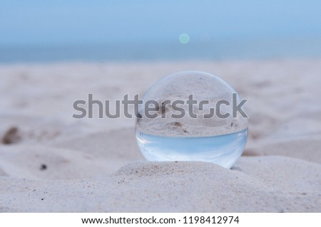 Beautiful Tropical Landscape seen through a Glass Orb. Glass orb by the sea and beach with waves crashing on shore. #1198412974