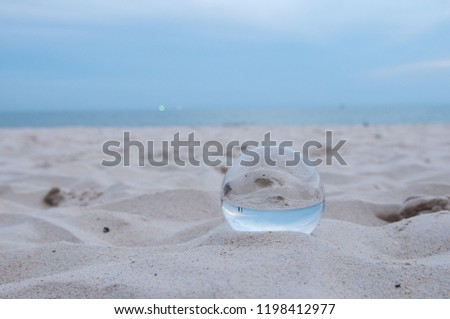 Beautiful Tropical Landscape seen through a Glass Orb. Glass orb by the sea and beach with waves crashing on shore. #1198412977