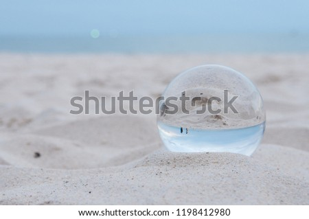 Beautiful Tropical Landscape seen through a Glass Orb. Glass orb by the sea and beach with waves crashing on shore. #1198412980