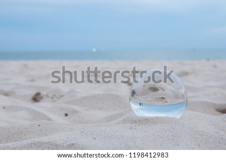 Beautiful Tropical Landscape seen through a Glass Orb. Glass orb by the sea and beach with waves crashing on shore. #1198412983