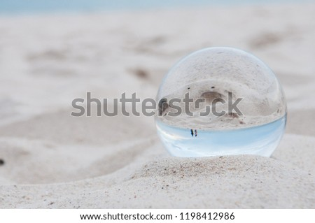 Beautiful Tropical Landscape seen through a Glass Orb. Glass orb by the sea and beach with waves crashing on shore. #1198412986