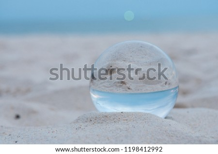 Beautiful Tropical Landscape seen through a Glass Orb. Glass orb by the sea and beach with waves crashing on shore. #1198412992