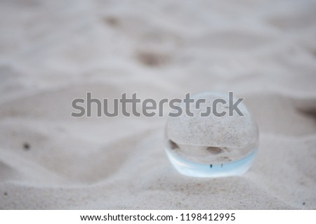 Beautiful Tropical Landscape seen through a Glass Orb. Glass orb by the sea and beach with waves crashing on shore. #1198412995