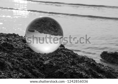 Beautiful Tropical Landscape seen through a Glass Orb. Glass orb by the sea and beach with waves crashing on shore. #1242856036
