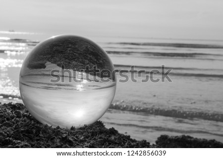 Beautiful Tropical Landscape seen through a Glass Orb. Glass orb by the sea and beach with waves crashing on shore. #1242856039