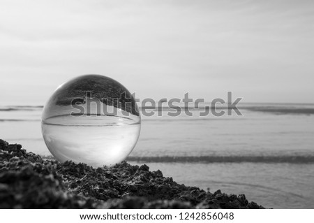 Beautiful Tropical Landscape seen through a Glass Orb. Glass orb by the sea and beach with waves crashing on shore. #1242856048