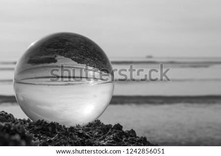 Beautiful Tropical Landscape seen through a Glass Orb. Glass orb by the sea and beach with waves crashing on shore. #1242856051