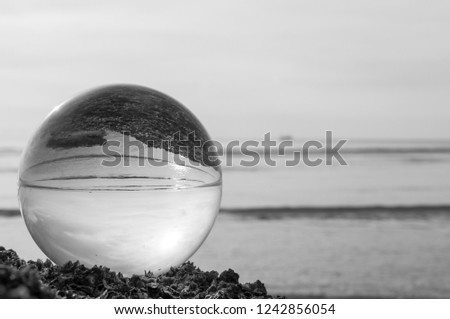Beautiful Tropical Landscape seen through a Glass Orb. Glass orb by the sea and beach with waves crashing on shore. #1242856054