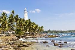 Beautiful tropical landscape with white Dondra Head Lighthouse and palms. Southern point of Sri Lanka coastline, Ceylon. Horizontal image