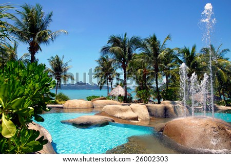 beautiful tropical swimming pool with fountain and view to ocean - stock photo