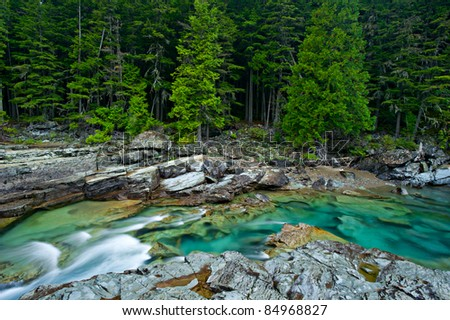Beautiful turquoise blue water flowing in McDonald Creek in Glacier National Park, Montana, USA.