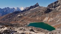 Beautiful turquoise colored mountain lake on the western ascent of Renjo La pass (5,430 m), Sagarmatha National Park, Nepal in the Himalayas, part of the challenging Three Passes Trek.