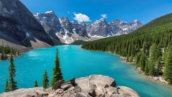 Beautiful turquoise waters of the Moraine lake with snow-covered rocky mountains in Banff National Park of Canada.