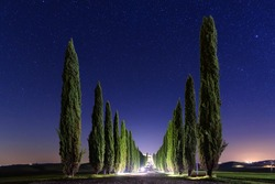 Beautiful Tuscany night landscape with star  sky, cypresses and shining road in green meadow. Natural outdoor amazing fantasy background.