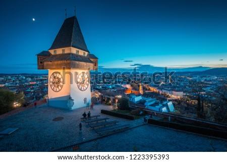 Beautiful twilight view of famous Grazer Uhrturm (clock tower) illuminated during blue hour at dusk, Graz, Styria region, Austria #1223395393