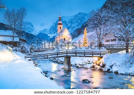Beautiful twilight view of Sankt Sebastian pilgrimage church with decorated Christmas tree illuminated during blue hour at dusk in winter, Ramsau, Nationalpark Berchtesgadener Land, Bavaria, Germany