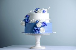 Beautiful two tiered white and blue wedding cake decorated with flowers sugar roses on the table. The concept of elegant holiday desserts
