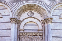 Beautiful tympanum over the entrance to  Pisa baptistery with mosaics, columns and reliefs. Architectural details. Medieval european art architecture. Facade of the building. Italy