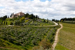 Beautiful typical and rural panorama with some wineyards, an old white gravel road and an old historic village. Photo made in Vertine near Radda in Chianti, Tuscany, Italy.