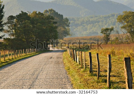 Beautiful un-paved country road lined with trees and fence.  Golden sunrise light on the area and hazy mountains are shown.