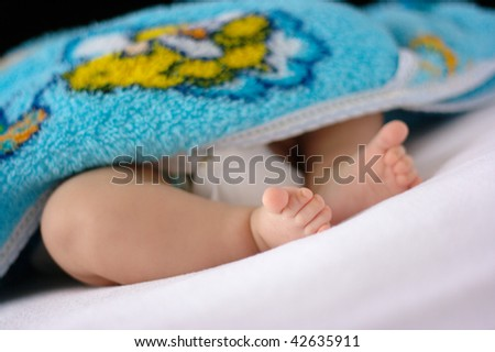Beautiful uncovered toddler's feet on white bedsheet